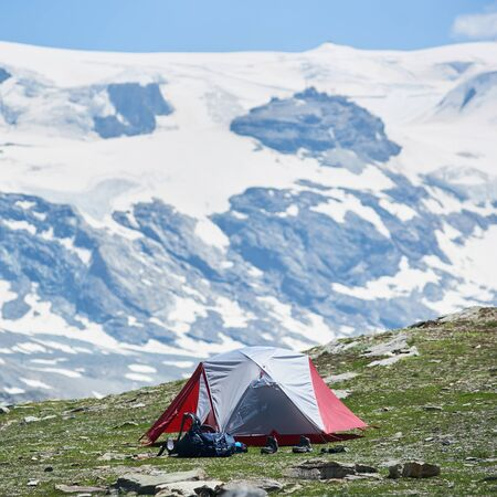 Beautiful view of mountain valley with tourist tent and hiker belongings. Picturesque scenery of camp tent with majestic rocky hills and peak on background. Concept of travelling, camping in Alps