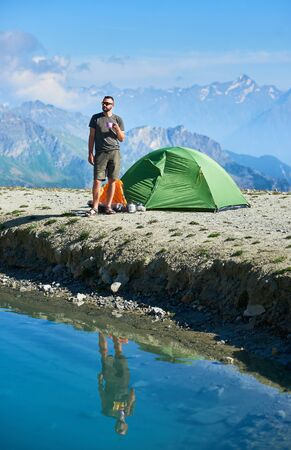 Traveler holding cup of tea while standing by tourist tent, beautiful blue lake in mountain valley. Male hiker in shorts reflecting in crystal water. Concept of travel, hiking, alpinism and camping.
