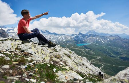 Tourist in t-shirt looking at beautiful mountains scenery and pointing with finger. Man reaching peak, sitting on stones. Wild nature with amazing views in sunny summer day. Sport tourism in Alps.