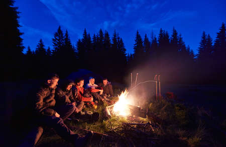 Company of young people is sitting around the fire against the backdrop of the silhouetted of large spruce trees and dark blue night sky. Camping in the forest. Vacation and tourism concept