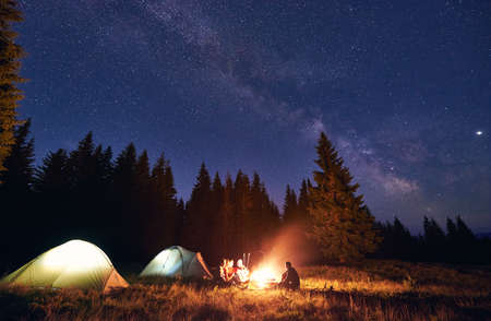 Company of five tourists, men and woman sitting by burning campfire near illuminated tents, enjoying beautiful night sky full of stars and bright Milky Way, warm summer night. Concept of tourism Banque d'images