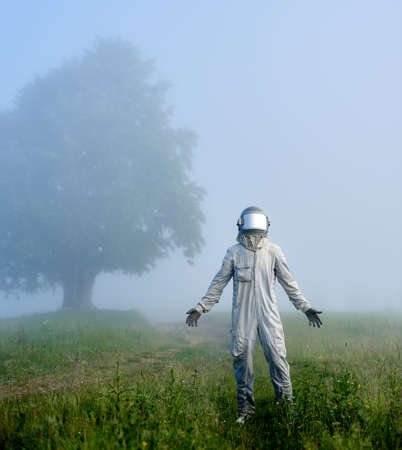 Full length vertical portrait of astronaut in white space suit and helmet standing on green glade with spread hands on foreground. Big old tree in the fog on background.