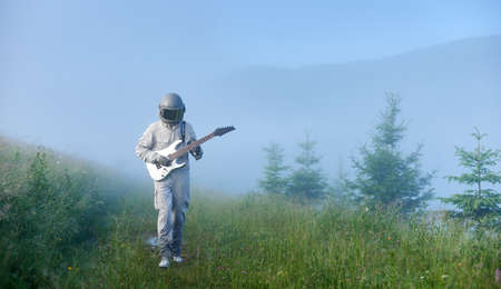 Front view of astronaut in space suit walking on grassy path and playing melody on guitar. Cosmonaut guitarist with musical instrument strolling down foggy meadow with green grass. 版權商用圖片