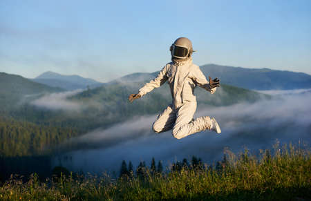 Full length of cosmonaut in space suit and helmet jumping in the air in grassy valley with foggy hills and blue sky on background. Concept of astronautics, freedom and nature. 版權商用圖片