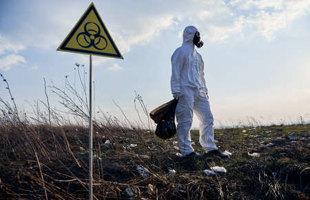 Full length of male ecologist in radiation suit and gas mask holding garbage bag, standing near biohazard warning sign on abandoned territory with trash. Concept of ecology, environmental pollution