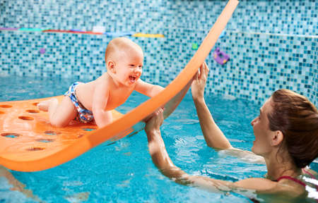 Snapshot of a very happy and playful swimming class with instructor. Cheerful baby boy is crawling on a floating mat with holes and playing with a caregiver