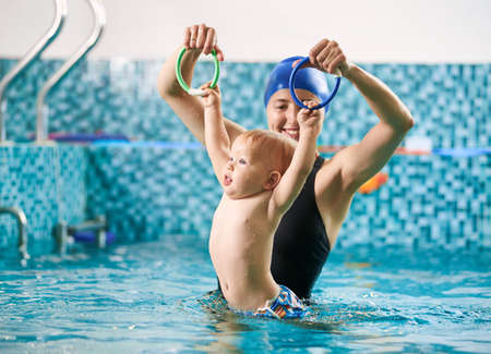 Swimming lesson for infants. Mother is training her baby boy in swimming pool using colorful rings, little boy is holding rings and floating in water. Concept of early development