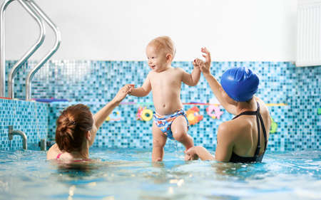 Back view of two women in swimming pool helping a small boy keep balance in water, smiling baby is standing in their hands. Concept of sport for kids Zdjęcie Seryjne