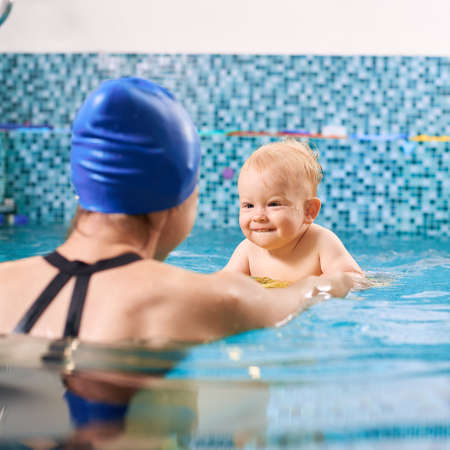 Woman wearing blue cap is standing with her back to the camera in pool smiling and pulling a cute little boy so he is trying to swim, boy is in focus
