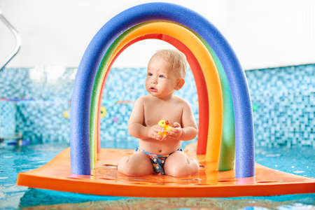 Portrait of a cute little boy wearing a diaper holding his rubber toy on a floating colorful construction in the swimming pool. Concept of healthy childhood