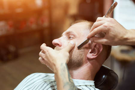 Close-up side view of hair stylists hands shaving his male customers beard with a barber shaving razor, warm light on the background
