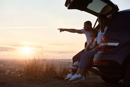 Side view of the family sitting in the car trunk outside the city on the hill watching the sunset, father is pointing on the horizon, copy space