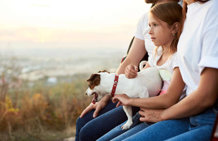 Close-up shot of the girl with her pet dog on her laps, sitting in the car trunk between her parents, family wearing white t-shirt and jeans enjoys a beautiful view from the hill