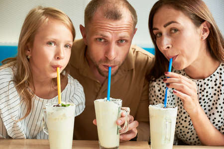 Portrait of father, mother and daughter drinking milkshakes with colorful straws in the cafe, family time, close-up 版權商用圖片