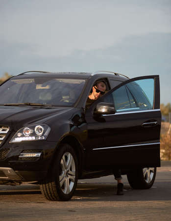 Young successful man wearing sunglasses is getting into his black car on the street under a blue sky, side view, copy space
