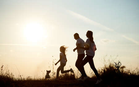 Silhouette young and beautiful family of three are jogging with their dog one by one outside the city on the village road on the setting sun, side view