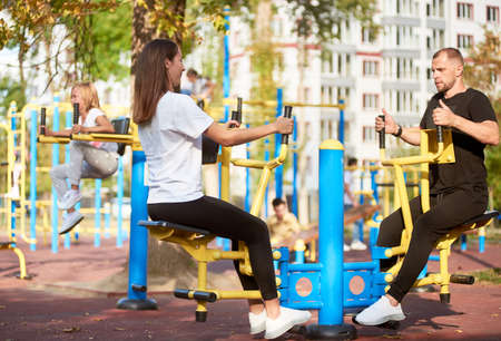 Mother and father are training legs and arms outdoors on the sport bars face to face, their daughter is doing abs on the background, sunny autumn weather