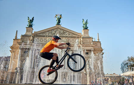 Extreme sportsman performing dangerous ride on mountain bike back wheel in front of fountain and opera house, side view, horizontal snapshot