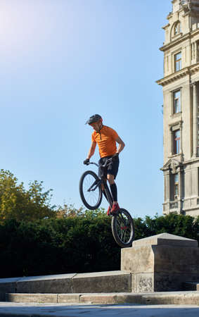 Trial biker standing on the back wheel of his mountain bike on a beautiful sunny day over blue sky, concept of active lifestyle 스톡 콘텐츠