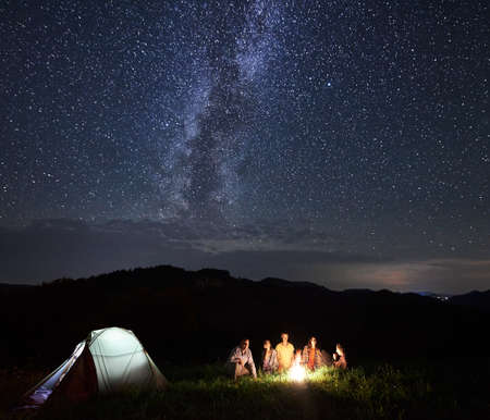 Night camping in the mountains. Group of tourists resting around campfire in summer, having small talks near illuminated tent under beautiful sky full of stars and Milky way