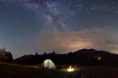 Night camping. Burning bonfire near the tent against backdrop of powerful mountains under starry night sky on which Milky Way is visible. Beautiful landscape of nature in the evening