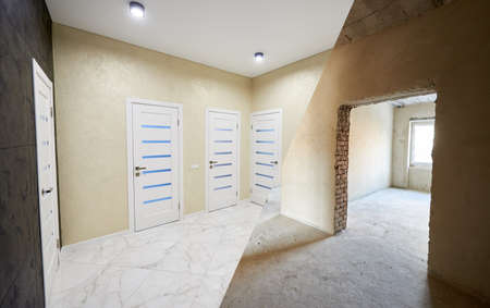 Horizontal snapshot of a room in a big apartment, before and after versions, modernized corridor with many closed white doors, spot lights on the ceiling in a light hallway Zdjęcie Seryjne