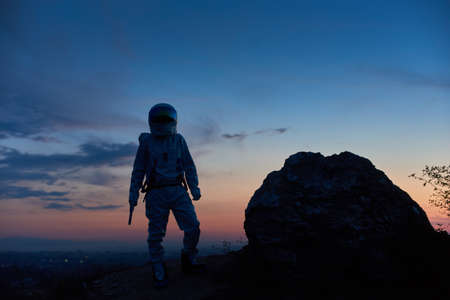 Silhouette of brave space traveler standing on rocky mountain with beautiful sunset on background. Cosmonaut wearing white space suit with helmet. Concept of space travel and beauty of twilight.
