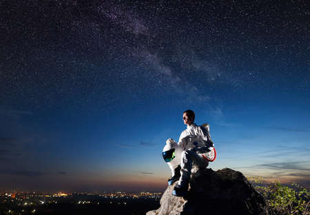 Side view of astronaut sitting on top of rocky hill and looking at beautiful night sky. Spaceman wearing space suit and holding helmet. Concept of astronautics and human space exploration.