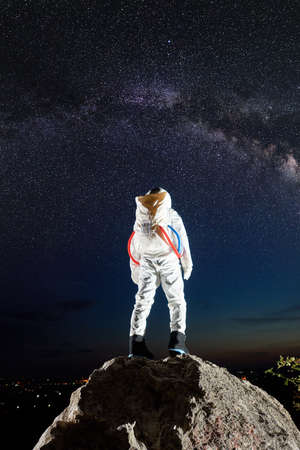 Back view of spaceman standing on top of rocky mountain and looking at beautiful night sky with stars. Space traveler wearing white space suit. Concept of cosmonautics, milky way and space activities. Zdjęcie Seryjne