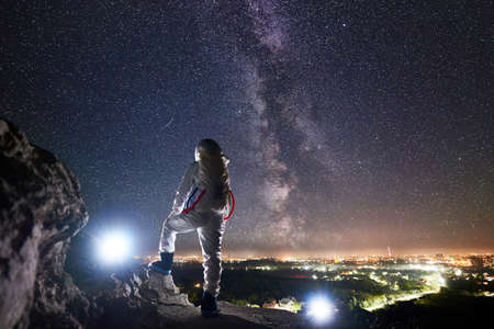 Back view of space traveler standing on rocky mountain and enjoying view of sky with stars, Milky way and night city. Mission specialist astronaut wearing white space suit. Concept of space traveling