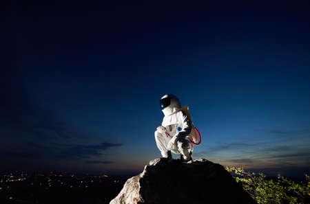 Brave spaceman hunkering down on top of mountain with mesmerizing blue sky on background. Cosmonaut wearing white space suit with helmet. Concept of space exploration and cosmonautics. Zdjęcie Seryjne