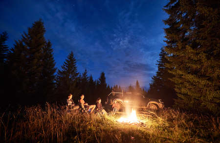Beautiful view of night blue sky over meadow with travelers near campfire. Tourists sitting in forest with tall coniferous trees and car on background. Concept of travelling and night camping.