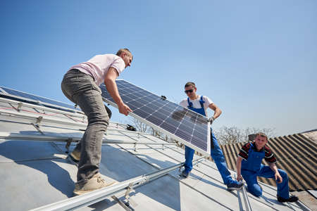Male engineers installing solar photovoltaic panel system. Three electricians lifting blue solar module on roof of modern house. Alternative energy sustainable resources ecology concept. Zdjęcie Seryjne