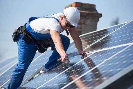 Male workers installing stand-alone solar photovoltaic panel system. Electricians mounting blue solar module on roof of modern house. Alternative energy ecological concept.