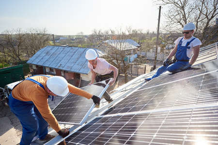 Male team workers installing stand-alone solar photovoltaic panel system. Electricians mounting blue solar module on roof of modern house. Alternative energy ecological concept.