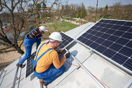 Male engineers installing solar photovoltaic panel system. Electricians mounting blue solar module on roof of modern house. Alternative energy sustainable concept. Zdjęcie Seryjne