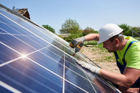Profile of professional technician working with screwdriver, connecting shiny solar photo voltaic panel to metal platform system on summer rural landscape and blue sky copy space background.