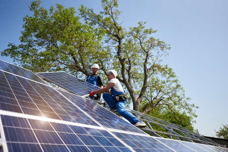 Two workers in protective helmet on steel platform installing heavy solar photo voltaic panel on green tree and blue sky background. Exterior solar panel system installation, dangerous job concept.