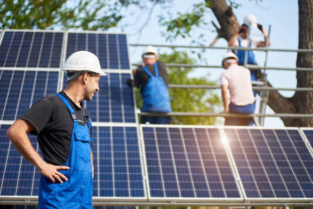 Profile of successful engineer technician standing in front of unfinished high exterior solar panel photo voltaic system blue shiny surface, looking at team of workers on high platform.
