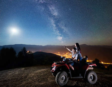 Young couple man and woman tourists riding atv quad motorbike on the top of mountain. Man pointing at beautiful night sky full of stars, full moon, Milky way, luminous village on background