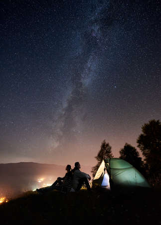 Silhouette of couple travellers having a rest at campfire beside camp and tourist tent under amazing night sky full of stars and Milky way. On the background starry sky, mountains and luminous town Фото со стока