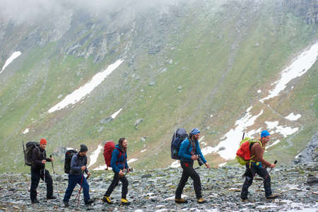Hikers team walking on rocky path with high mountain slope on background. Male tourists with backpacks and trekking poles hiking in mountainous region. Concept of travelling, tourism, active leisure.