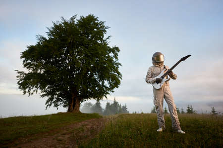 Astronaut guitarist in space suit and helmet with musical instrument playing guitar, standing in hillside meadow with beautiful tree and sky on background. Concept of music, cosmonautics and nature.