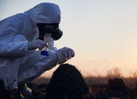 Side view, crouched male scientist wearing protective suit, gas mask, gloves collecting samples from scorched anthill, holding glass flask with blue liquid and tweezers on sunset. Concept of ecology