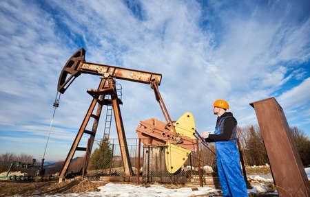 Petroleum engineer in work overalls and helmet holding clipboard, checking oil pumping unit, making notes. Man standing near oil pump jack. Concept of oil extraction and petroleum industry.
