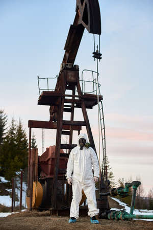 Full length of male ecologist standing on territory of oil field with oil pump rocker-machine on background, wearing white protective suit, gas mask, gloves. Concept of ecology and petroleum industry