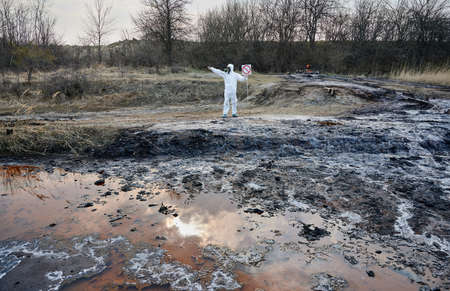 Researcher in white protective suit and gas mask installing warning sign, no entry sign, on contaminated territory. Rusted dirty muddy water for analysis. Concept of ecological disaster Archivio Fotografico