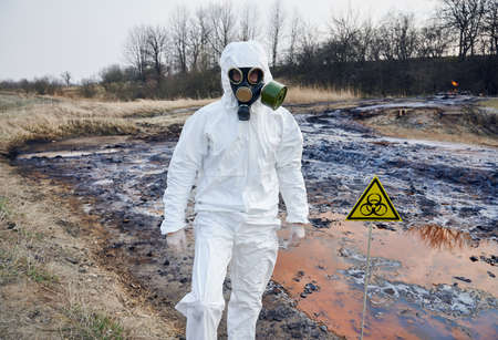Scientist wearing white protective coverall and gas mask standing next to a biohazard sign at contaminated water. Concept of ecological disaster and exclusion zone