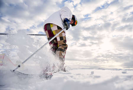 Low angle view snapshot of skiers legs making a jump up on white snowy surface against beautiful cloudy sky. Man wearing colorful ski pants and white winter jacket. Concept of winter sport activities