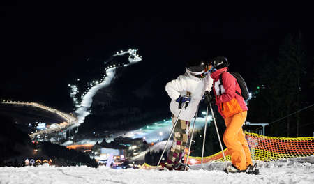Couple of tourists standing on the hill kissing against amazing night background of illuminated ski pistes, copy space. Concept of active lifestyle, night skiing and relationships. Stock Photo